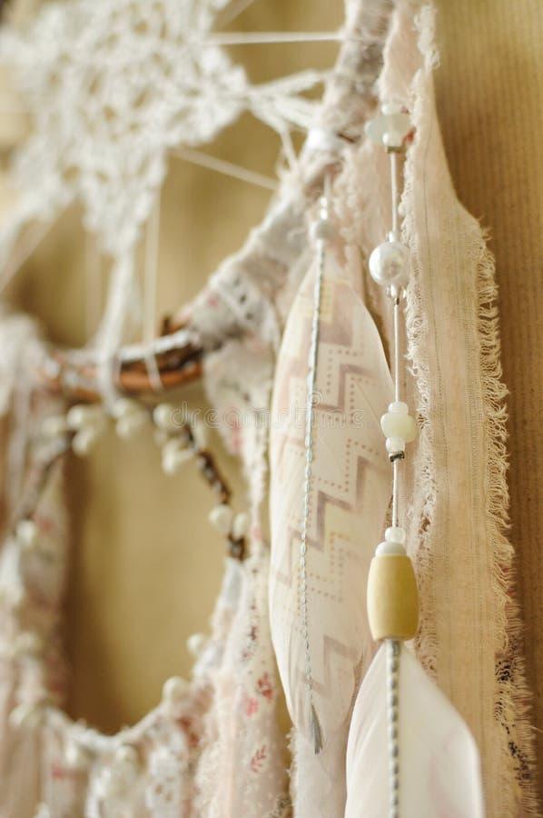 与钩针编织小垫布雪花的特写镜头细节手工制造dreamcatcher和在工艺纸背景的被绘的羽毛 免版税库存照片