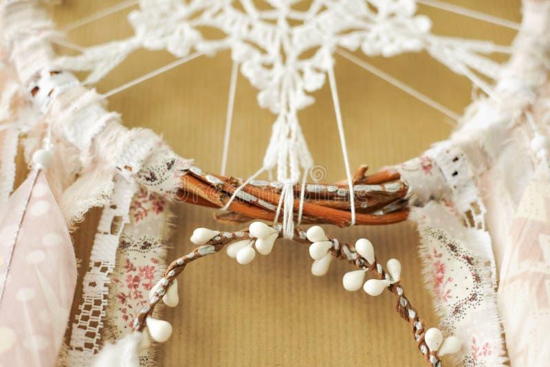 与钩针编织小垫布雪花的特写镜头细节手工制造dreamcatcher和在工艺纸背景的被绘的羽毛 库存图片