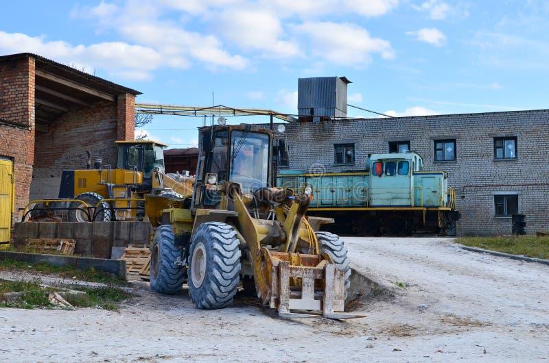与铁桶的黄色轮子装载者 在建造场所的挖掘机 图库摄影