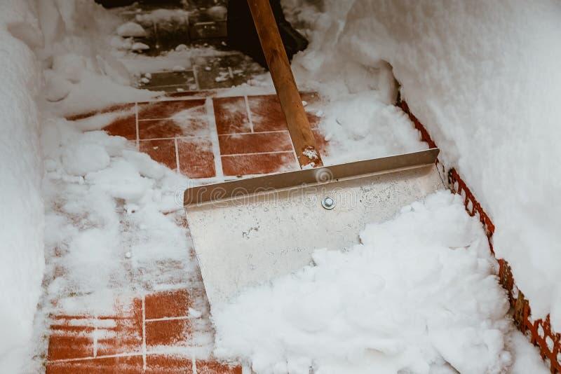 与铁铁锹的积雪的清除 使用木把柄 围场的冬天清洁从雪的 大量降雪 免版税库存图片