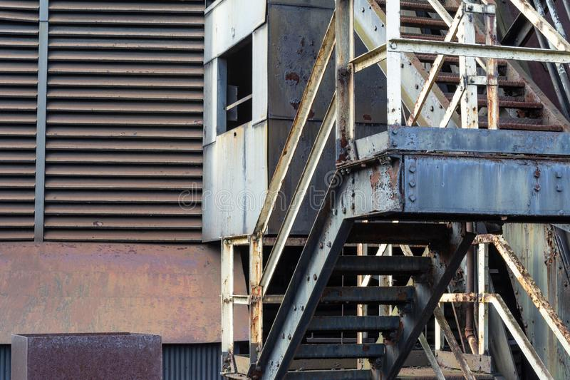 与铁锈和剥油漆的老工业台阶,出气孔,坚实和波纹状的房屋板壁 免版税库存图片