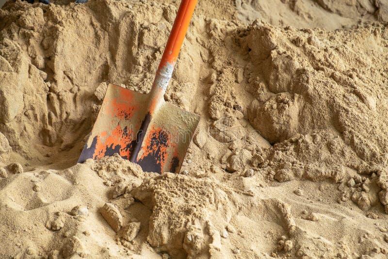 与铁锹的建筑沙子在石膏工的建筑工作站点 库存照片