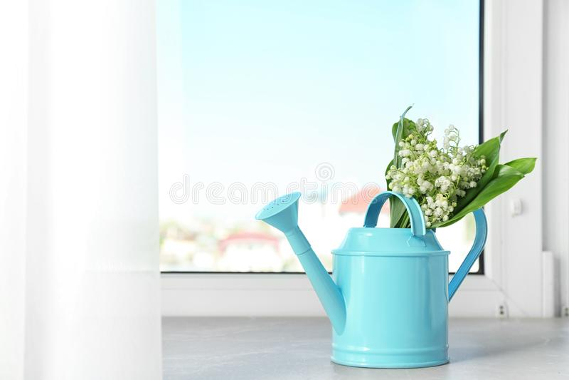 与铃兰花束的喷壶在窗台 库存照片