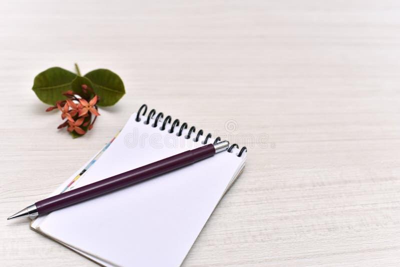与铅笔、花和心脏的笔记薄在桌上 免版税库存照片