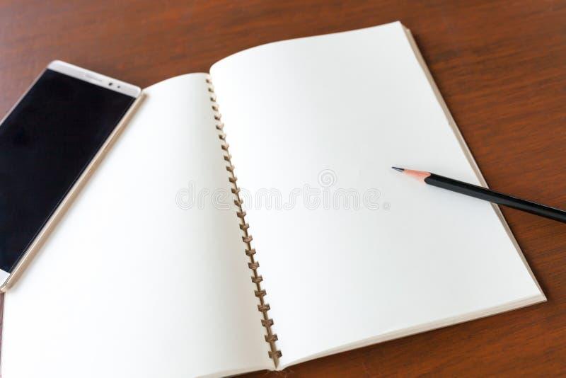 与铅笔和智能手机的空白的笔记本在木桌backg 库存照片