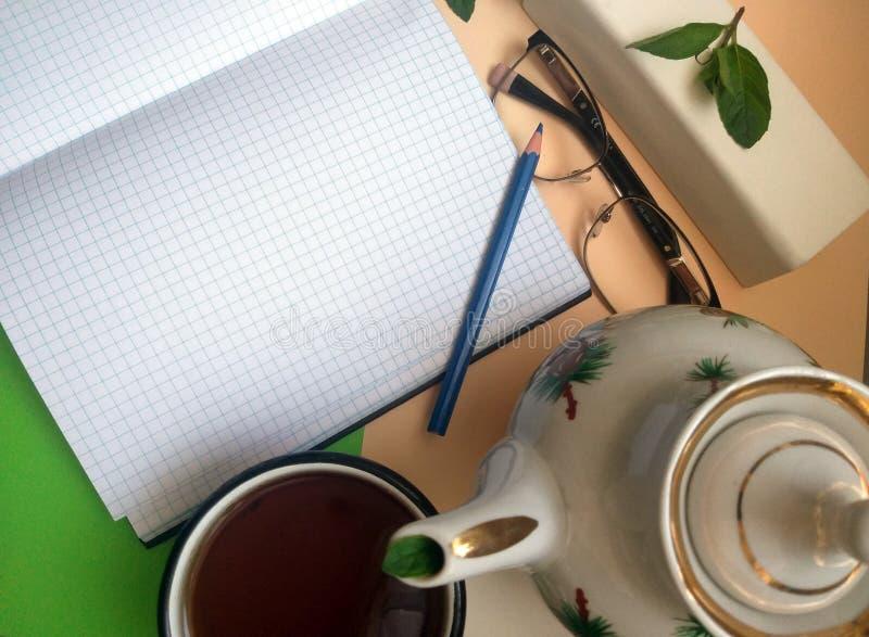 与铅笔和玻璃的被打开的笔记本页 库存图片