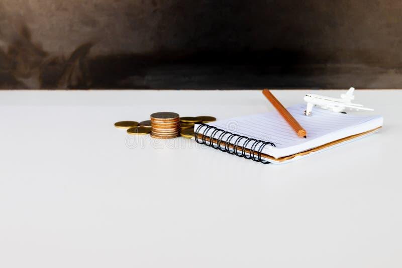与铅笔和硬币堆的笔记本在黑背景的白色 图库摄影