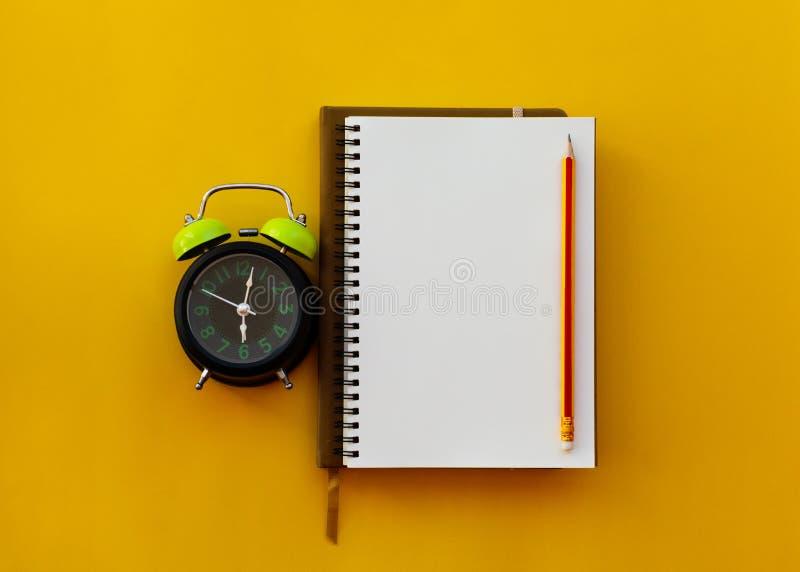 与铅笔和闹钟的空白的白色笔记薄在黄色背景 库存照片