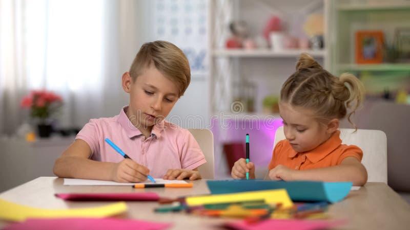 与铅笔的可爱的男孩和女孩图画,坐在桌上,幼儿园 免版税库存图片