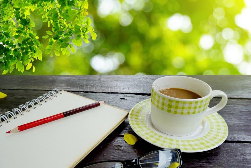 与铅笔的咖啡和笔记本页在自然绿色叶子的木桌上 免版税图库摄影
