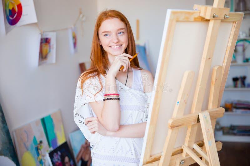 与铅笔的愉快的被启发的女性艺术家图画在艺术课 免版税库存图片