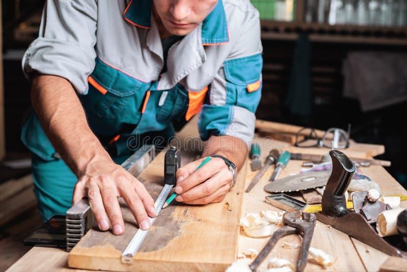 与铅笔的男性木匠锯裁减的笔记使用在委员会的测量的磁带,标记,有铅笔的男性手和测量的磁带c 免版税图库摄影