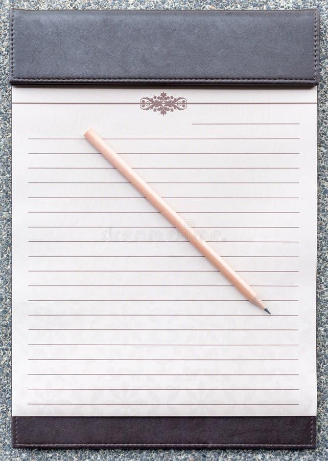 与铅笔的空白的笔记薄在棕色剪贴板 库存照片