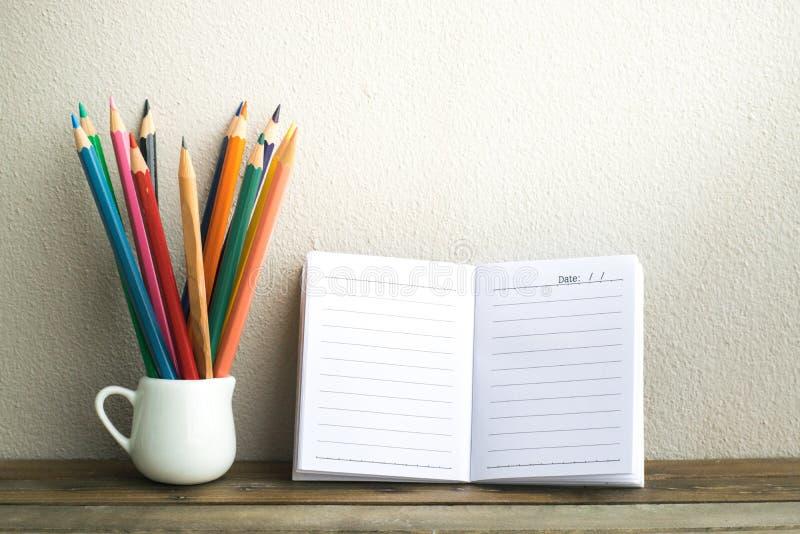 与铅笔的笔记薄在木委员会背景 使用教育的墙纸,企业照片 注意到书的产品与 免版税库存图片