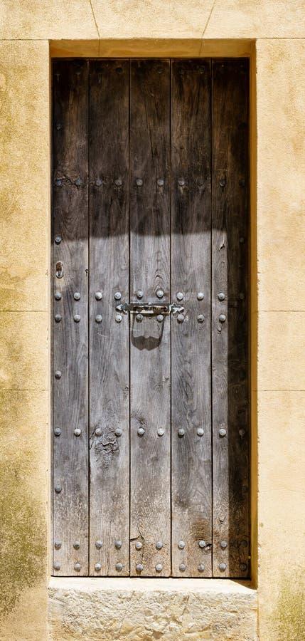 与铆钉的巨型的木门在这是被风化的石头框架  免版税库存照片
