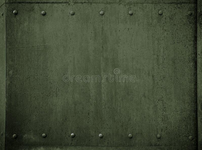 与铆钉的老军事金属绿色装甲背景 免版税图库摄影