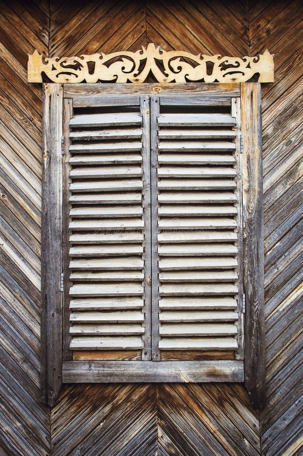 与铰链和被雕刻的快门的老被风化的木闭合的窗口 减速火箭 库存图片