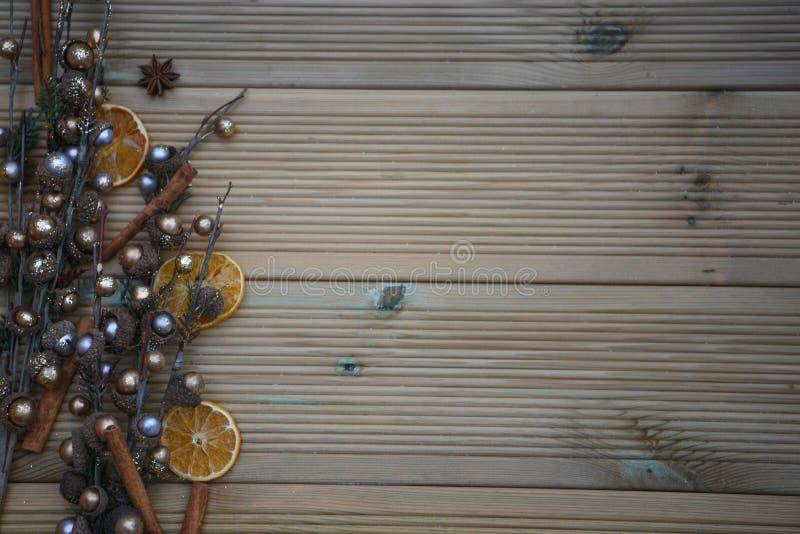 与银和金子的圣诞节摄影上色了橡子在自然土气木背景的树装饰品用八角香料 库存照片