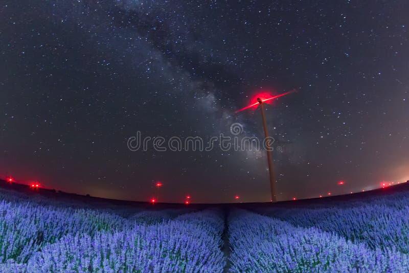 与银河的美丽的繁星之夜天空在淡紫色和风轮机红灯的领域  库存图片