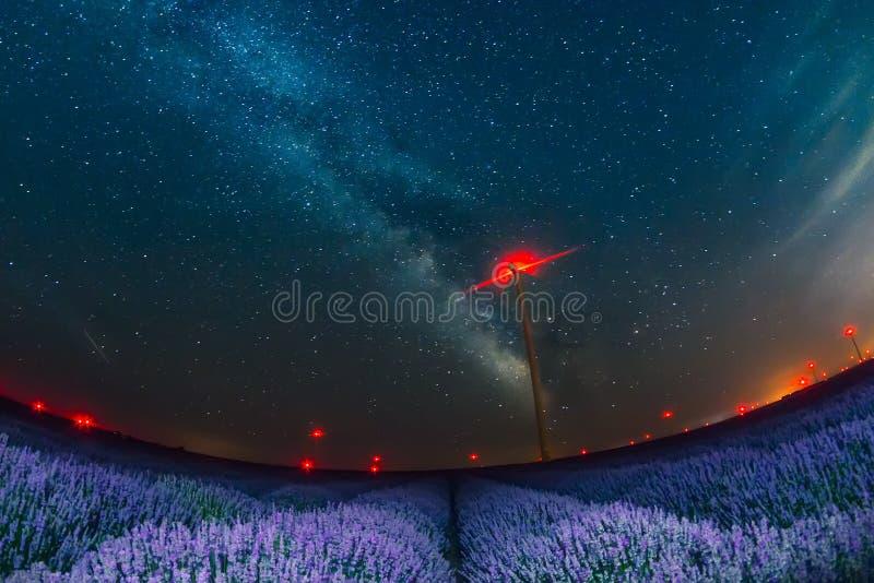 与银河的美丽的繁星之夜天空在淡紫色和风轮机红灯的领域  免版税库存图片