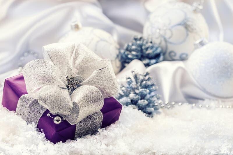 与银色丝带和背景圣诞节装饰的紫色圣诞节包裹-圣诞节球杉木锥体白色缎和丝毫 免版税库存照片