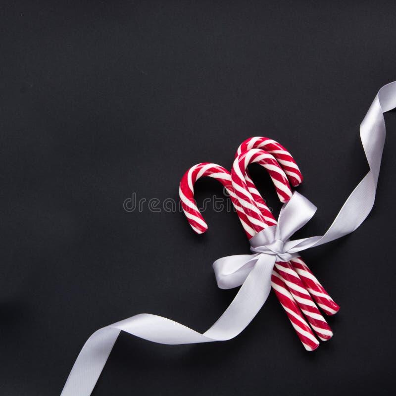 与银色丝带的圣诞节糖果在黑背景 抽象空白背景圣诞节黑暗的装饰设计模式红色的星形 顶视图和拷贝空间 库存照片