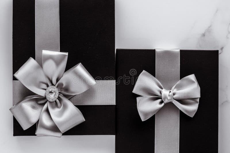 与银色丝绸丝带和弓的豪华节日礼物在大理石背景 库存图片
