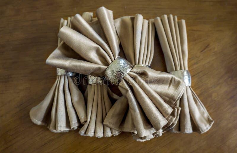 与银色圆环花梢可折叠的金黄餐巾弓为假日 免版税图库摄影