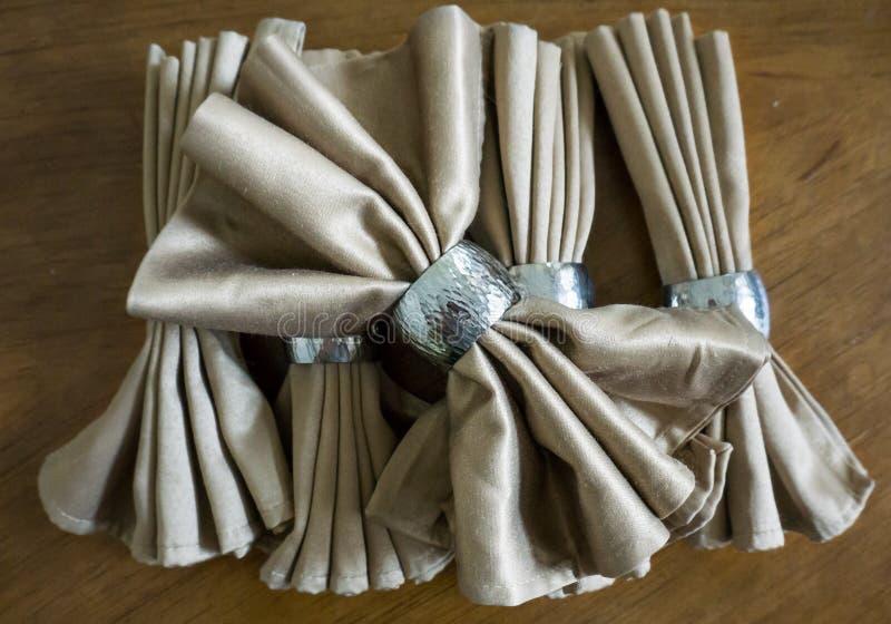与银色圆环花梢可折叠的金黄餐巾弓为假日 库存图片