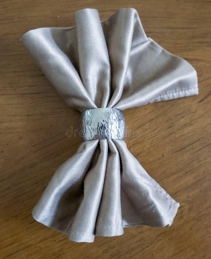 与银色圆环花梢可折叠的金黄餐巾弓为假日 免版税库存图片