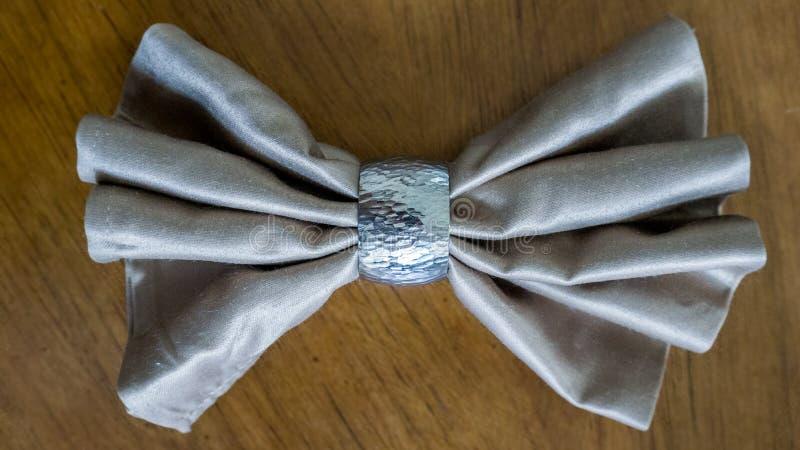 与银色圆环花梢可折叠的金黄餐巾弓为假日 库存照片