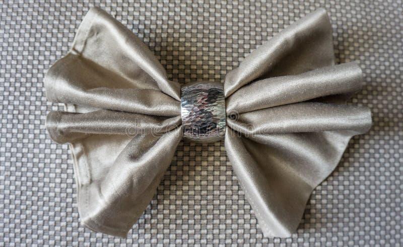 与银色圆环花梢可折叠的金黄餐巾弓为假日 免版税库存照片
