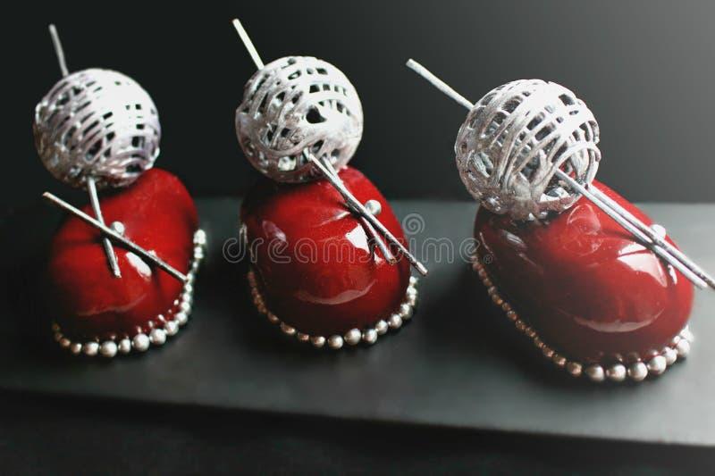 与银色羊毛球装饰和果仁巧克力的红色圣诞节莓果点心 图库摄影