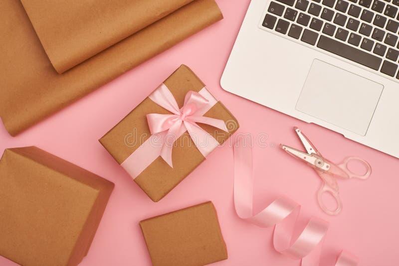 与银色膝上型计算机的礼品包装材料集合在桃红色flatlay 免版税图库摄影