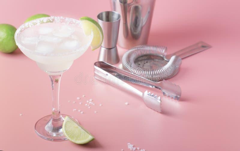 与银色龙舌兰酒、利口酒、柠檬汁、糖浆、盐和冰,欢乐时髦桃红色的石灰玛格丽塔酒酒精鸡尾酒 免版税库存照片