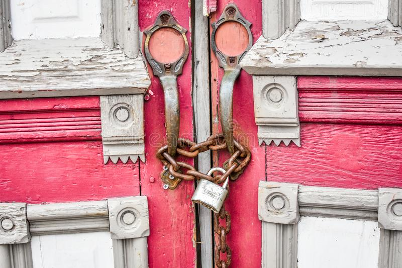 与链子和锁的被放弃的红色教会门 免版税图库摄影