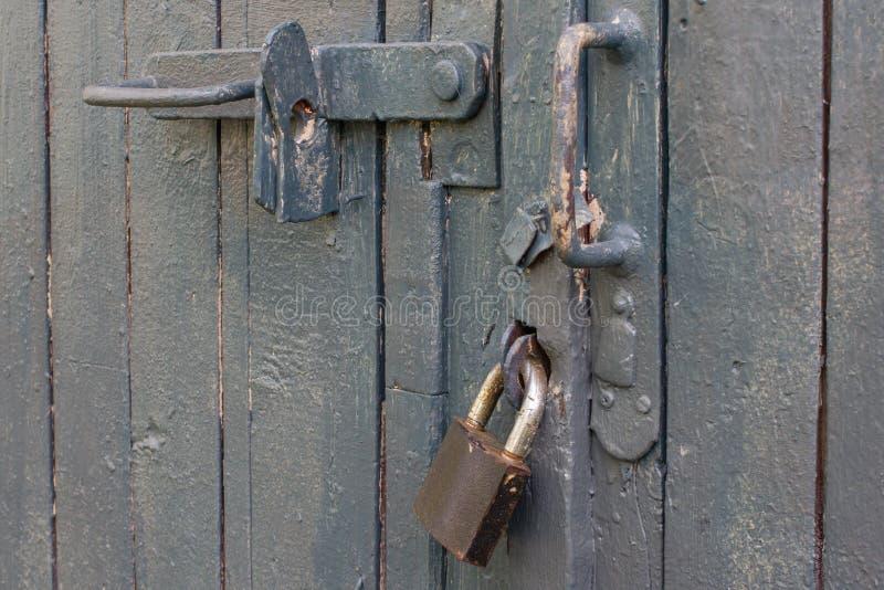 与锁的老灰色门 免版税库存图片