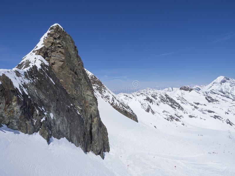 与锋利的山峰的冬天风景和积雪的倾斜和滑雪道与享受春天好日子的滑雪者在 库存图片