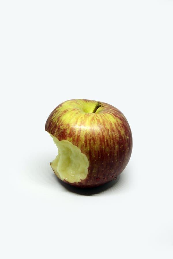 与错过在白色背景的绿色叶子的红色苹果叮咬 库存照片