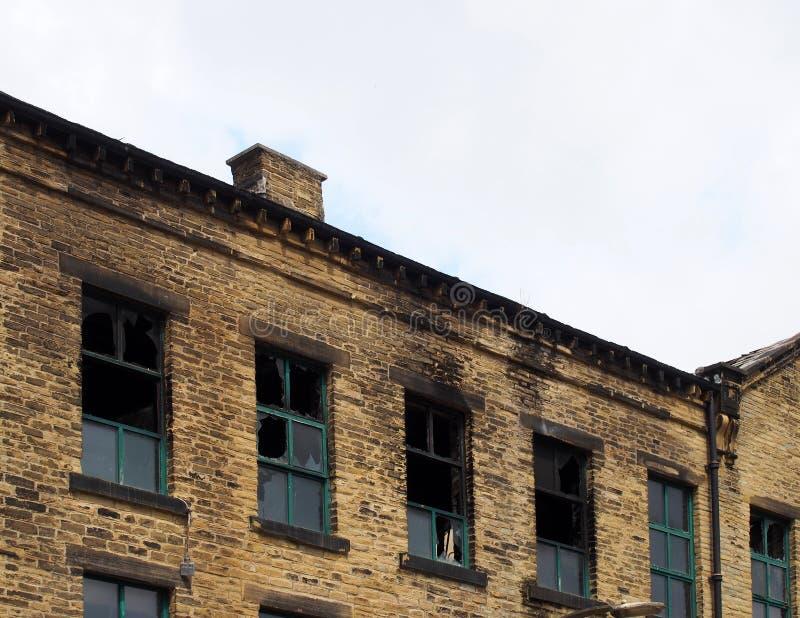 与错过的屋顶和残破的窗口的被放弃的遗弃工业仓库大厦 库存图片