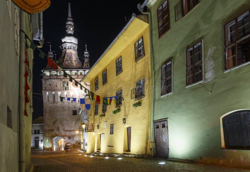 与锡吉什瓦拉中世纪镇的塔时钟的夜景,在罗马尼亚 图库摄影