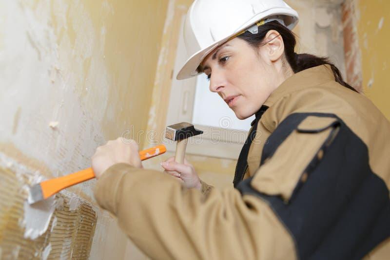 与锤子和凿子的女性建造者在工作 库存照片