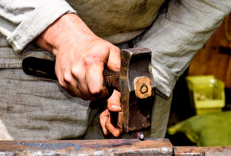 与锤子的铁匠运作的金属 免版税库存图片