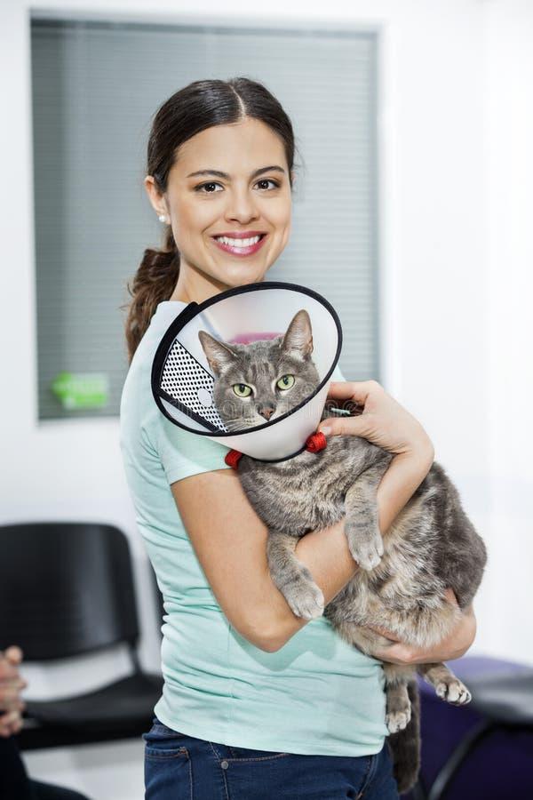 与锥体的中间妇女运载的猫在诊所 免版税库存图片