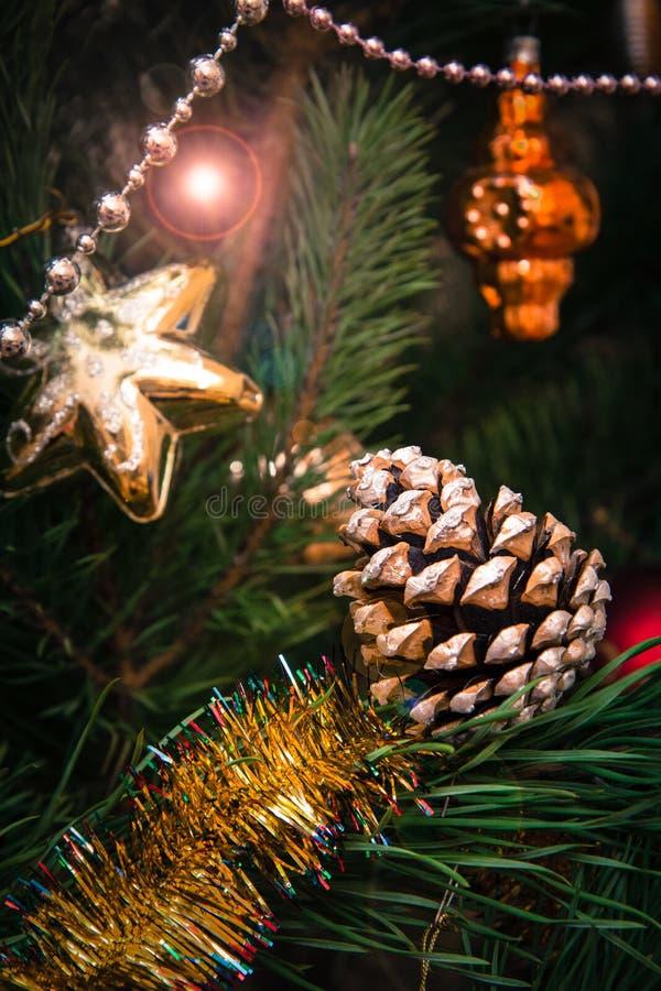 与锥体的云杉的分支和球,在背景的欢乐光 免版税图库摄影