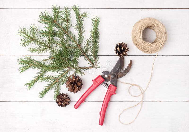 与锥体的绿色冷杉分支在白色木背景圣诞节和新年背景红色Pruner顶视图平的位置 免版税库存图片