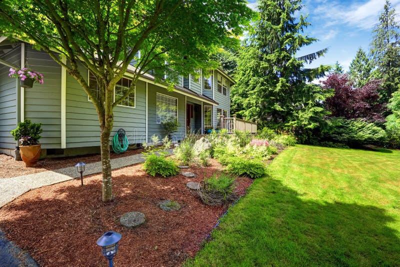 与锯木屑花床和草坪的美好的风景设计 库存照片
