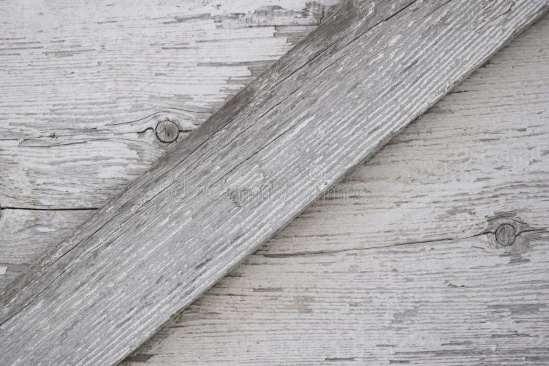 与镇压、结和剥落的白色油漆的灰色木表面 免版税图库摄影