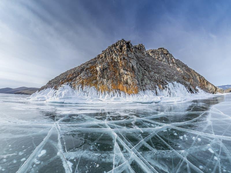与镇压和裂口的透明冰在冻峭壁附近的贝加尔湖的与雪和树冰盖的石头 库存图片