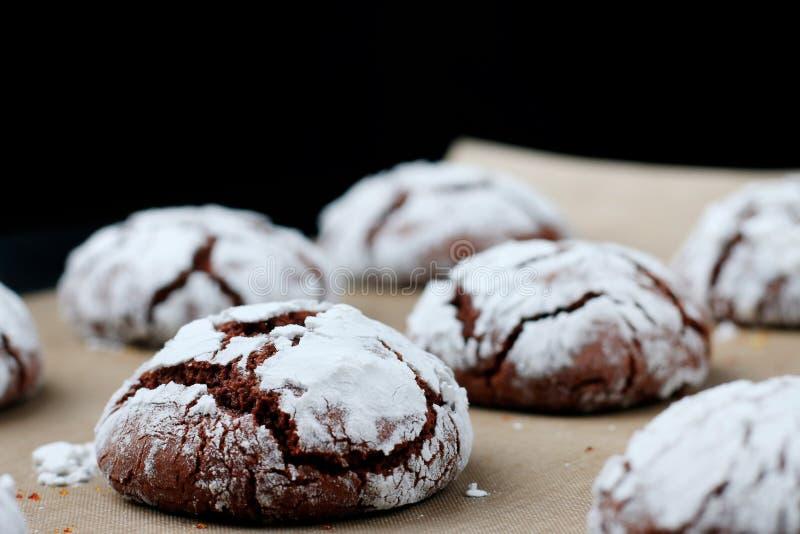 与镇压的巧克力饼干在烘烤的纸和iolated在黑色 破裂的巧克力饼干 免版税库存照片